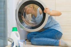 Mulher que olha para dentro da máquina de lavar foto de stock
