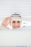 Mulher que olha para fora através das cortinas Foto de Stock
