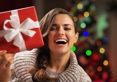 Mulher que olha para fora da caixa atual na frente das luzes de Natal Fotografia de Stock