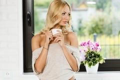 Mulher que olha para fora a janela com café quente Imagem de Stock Royalty Free