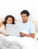 Mulher que olha seu marido que trabalha em seu portátil Imagem de Stock