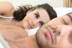 Mulher que olha seu sono do marido fotografia de stock