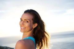 Mulher que olha sobre o ombro com o mar no fundo fotos de stock royalty free