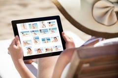 Mulher que olha suas imagens na tabuleta digital Fotos de Stock Royalty Free