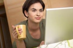 Mulher que olha a tela do portátil que sorri em casa imagens de stock royalty free