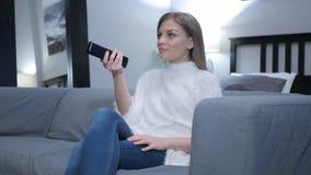 Mulher que olha a tevê, canais em mudança com telecontrole foto de stock