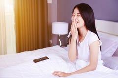 Mulher que olha a tevê rir tendo o divertimento com controlo a distância na cama fotos de stock royalty free
