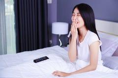 Mulher que olha a tevê rir tendo o divertimento com controlo a distância na cama foto de stock