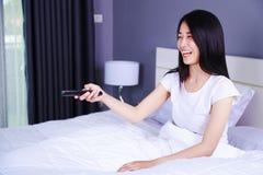 Mulher que olha a tevê rir tendo o divertimento com controlo a distância na cama imagem de stock royalty free