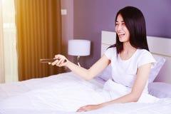 Mulher que olha a tevê rir tendo o divertimento com controlo a distância na cama fotos de stock