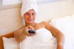 Mulher que olha a tevê em sua cama Fotos de Stock Royalty Free