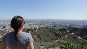 Mulher que olha a vista de uma cidade da parte superior de uma montanha video estoque