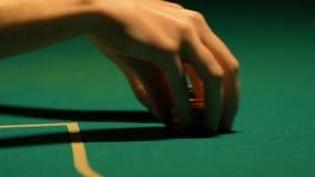 Mulher que põe últimas microplaquetas de pôquer sobre a tabela de jogo, fazendo a aposta tudo, close-up filme