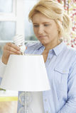Mulher que põe a ampola da baixa energia na lâmpada em casa Foto de Stock Royalty Free