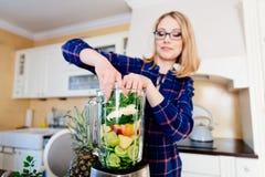 Mulher que põe frutas e legumes no misturador eletrical fotografia de stock