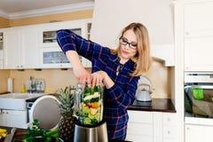 Mulher que põe frutas e legumes no misturador eletrical imagem de stock
