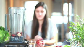 Mulher que põe frutos no misturador para misturar-se video estoque