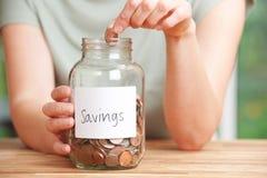 A mulher que põe a moeda no frasco etiquetou economias Foto de Stock