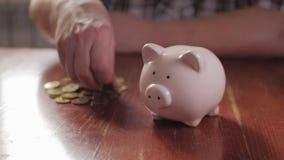 Mulher que põe a moeda no mealheiro, conceito de salvamento do dinheiro As necessidades futuras emprestam o crédito da educação o video estoque