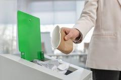 Mulher que põe o copo de papel usado no escaninho de lixo no escritório moderno Reciclagem de resíduos fotografia de stock royalty free