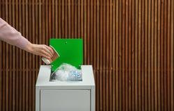 Mulher que põe o copo de papel usado no escaninho de lixo sobre o fundo de madeira, close up com espaço para o texto imagem de stock royalty free
