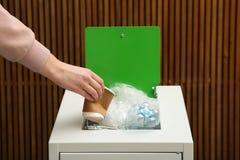 Mulher que põe o copo de papel usado no escaninho de lixo sobre o fundo de madeira Reciclando o conceito imagem de stock royalty free