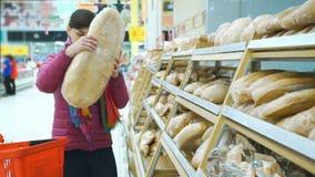 Mulher que põe o pão no cesto de compras video estoque