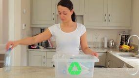 Mulher que põe o plástico no escaninho de reciclagem video estoque