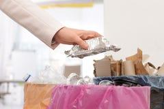 Mulher que põe o recipiente usado da folha no escaninho de lixo no escritório Reciclagem de resíduos fotografia de stock