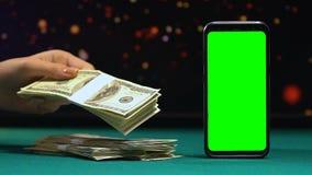 Mulher que põe pacotes de dólares sobre a mesa, app de aposta em linha, lucro grande video estoque