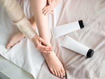 Mulher que põe a pomada ou o creme do creme hidratante sobre seus pés Cuidado de pele foto de stock royalty free