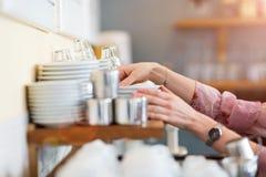 Mulher que põe pratos limpos para secar imagem de stock