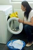 Mulher que põe a roupa na máquina de lavar Imagens de Stock Royalty Free