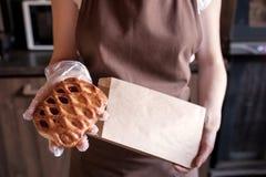 Mulher que põe a torta doce no saco de papel fotos de stock