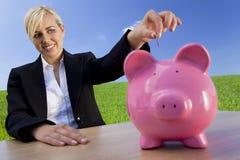 Mulher que põr a moeda no banco Piggy cor-de-rosa Foto de Stock