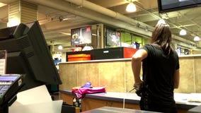 Mulher que paga calças de Adidas no contador de verificação geral video estoque