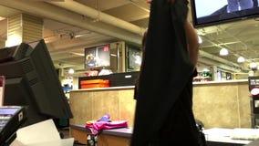 Mulher que paga calças de Adidas no contador de verificação geral filme