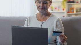 Mulher que paga com o cartão de crédito no portátil, aplicação de serviço bancário fácil filme