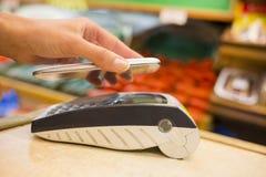 Mulher que paga com tecnologia do nfc no telefone celular, compra, supe Imagens de Stock