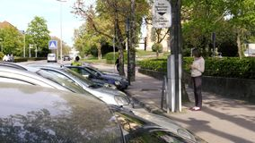 Mulher que paga estacionar na máquina alemão do pagamento do bilhete de estacionamento filme