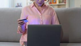 Mulher que paga a verificação com o cartão de crédito no portátil, pagamento de imposto em linha conveniente video estoque