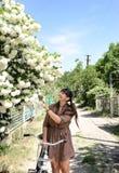 Mulher que para para admirar uma árvore na flor imagens de stock