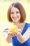 Mulher que passa a laranja Fotos de Stock Royalty Free