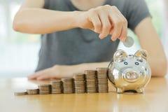 Mulher que põe uma moeda em um dinheiro-caixa-fim u Imagens de Stock Royalty Free