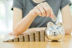 Mulher que põe uma moeda em um dinheiro-caixa-fim u Fotos de Stock Royalty Free