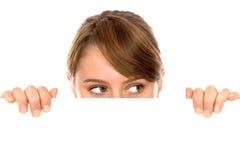 Mulher que peeping sobre um quadro de avisos em branco Fotografia de Stock