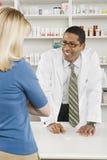 Mulher que pegara medicamentos de venta com receita na farmácia Fotos de Stock