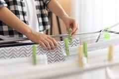 Mulher que pendura a lavagem para fora para secar fotografia de stock