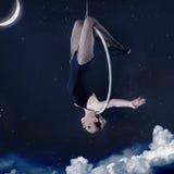 Mulher que pendura upside-down na aro aérea na noite fotografia de stock