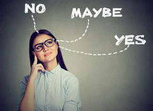 A mulher que pensa fazendo uma escolha tem dúvidas fotografia de stock